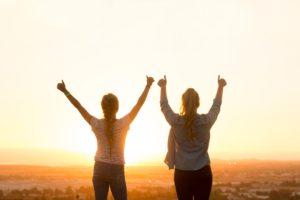 夕日の前で両手を上げる二人