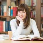 図書館で本を広げて座っている女子大生1