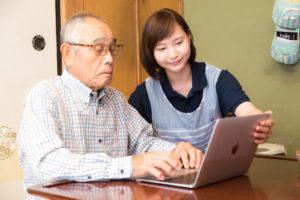 パソコン講習中の高齢者と介護士